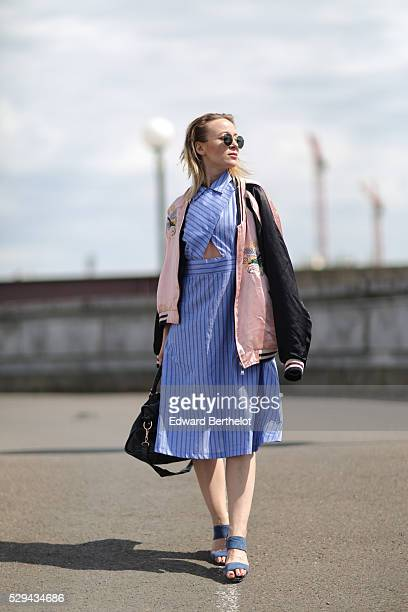 Amelie Lloyd is wearing a Sandro blue dress Comptoir des Cotonniers blue shoes a Zara black and pink bombers coat Ray Ban sunglasses and a Balenciaga...