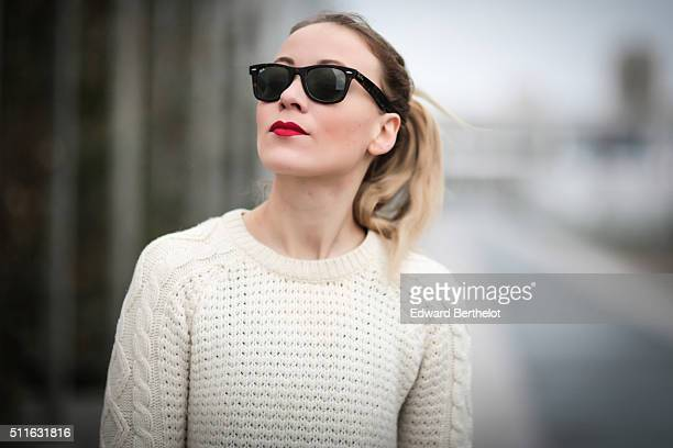 Amelie Lloyd wears a Balenciaga bag Rayban sunglasses and a Mango pull over sweater during a street style session on February 21 2016 in Paris France