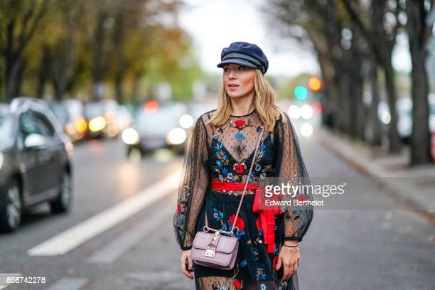 Amelie Lloyd wears a beret hat a Valentino bag a black lace mesh outfit with flower prints red shoes outside John Galliano during Paris Fashion Week...
