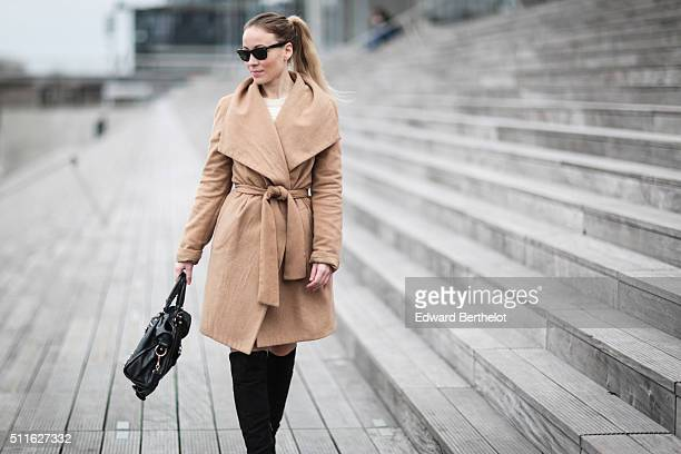 Amelie Lloyd wears a Mango coat Forever 21 boots a Balenciaga bag and Rayban sunglasses during a street style session on February 21 2016 in Paris...