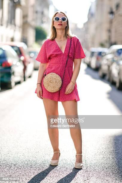 Amelie Lloyd wears a Zara pink dress a Zara straw bag Bershka sunglasses and HM heels on June 18 2017 in Paris France