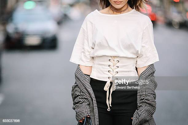 Amelie Lloyd wears NewLook black shiny boots Other Stories black pants a Zara white short sleeves lace corset top a Zara Prince de Galle long coat a...