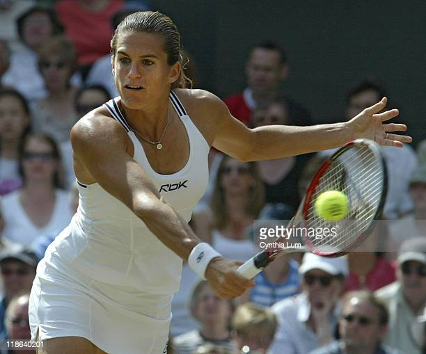 Amelie Mauresmo hits a return versus Justine Henin-Hardenne in the Ladies Finals of the 2006 Wimbledon Championships at the All England Lawn Tennis &...