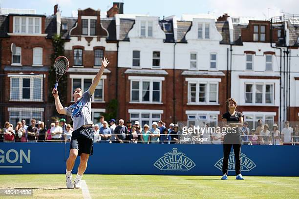 Amelie Mauresmo looks on as Andy Murray of Great Britain warms up on the practice courts on day three of the Aegon Championships at Queens Club on...