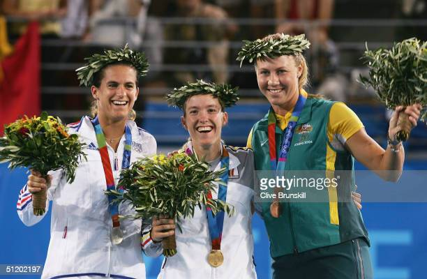 Amelie Mauresmo of France , Justine Henin-Hardenne of Belgium and Alicia Molik of Australia wave to the crowd during the medal ceremony for the...