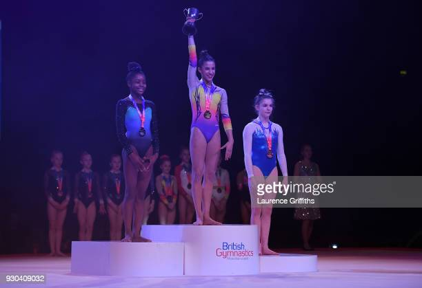 Amelie Morgan of The Academy recieves her gold medal for Vault alongside Ramiyah Kofi of Notts Gymnastics Academy and Scarlett Williams of Robin Hood...