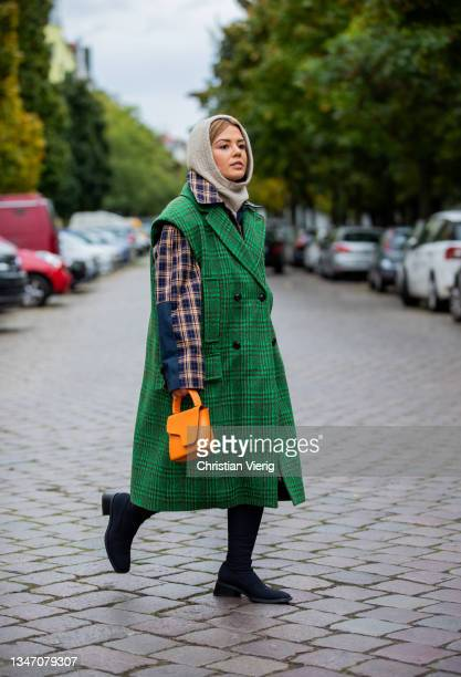 Amelie Stanescu is seen wearing Balaclava from Zara, Coat and green Vest from Baum und Pferdgarten, Shoes Vagabond Shoemakers, Bag ATP Atelier on...