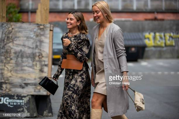 Amelie Stanescu wearing Loewe belt, dress with print and Tina Haase wearing grey coat, beige dress, Fendi bag, boots is seen outside Day Birger et...