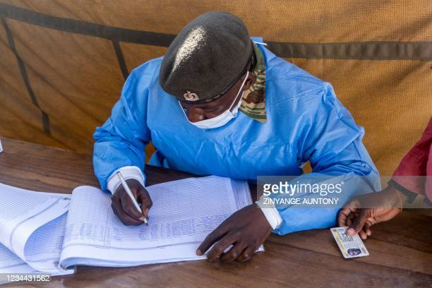 Amember of the Zimbabwe national Army goes through a verification of a civilianÕs particulars before inoculation of the COVID-19 vaccine during the...