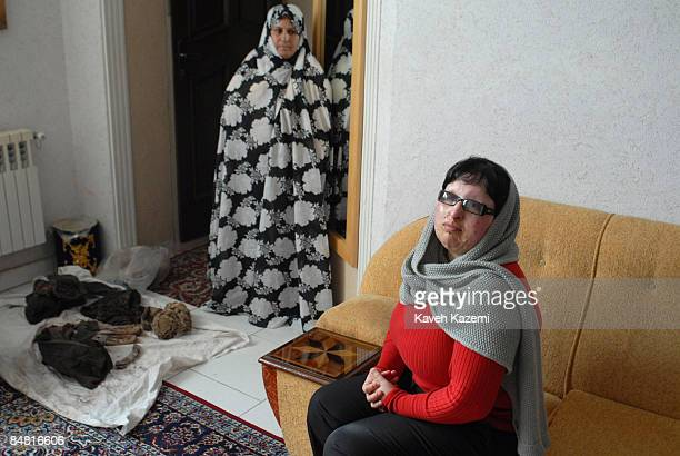 Ameneh Bahrami's mother stands in front of her clothing that was splashed by acid on the day of incident while Ameneh sits on a sofa in their Tehran...