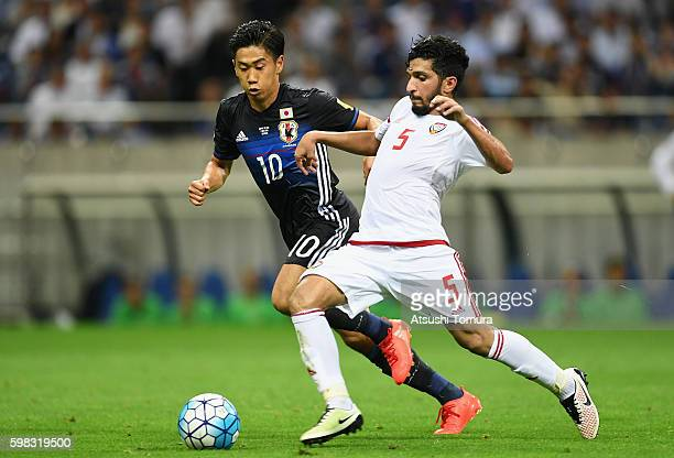 Amer Abdulrahman of the United Arab Emirates and Shinji Kagawa of Japan compete for the ball during the 2018 FIFA World Cup Qualifier Final Round...