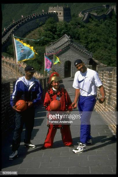 Amer basketball pros Alonzo Mourning Anfernee Penny Hardaway w costumed guard at Great Wall taking time out fr playing against Chinese natl team