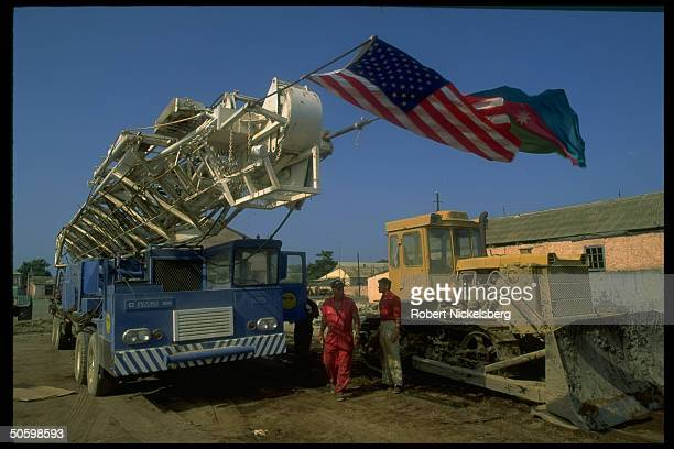 Amer Mega Oil Corp workers w TX co crane truck flying US Azeri flags in workover contract w Azeri govt