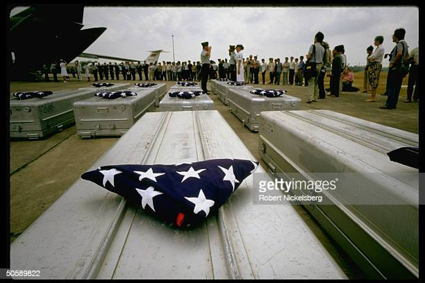 Amer repatriation ceremony for Vietnam War dead/MIA's w US mil personnel saluting aluminum coffins on airport tarmac