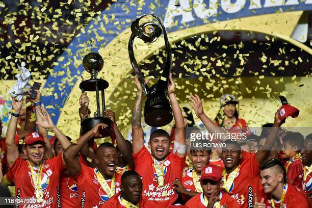 America de Cali's players celebrate with the trophy after defeating Atletico Junior to win the Colombian First Division Football Championship at the...