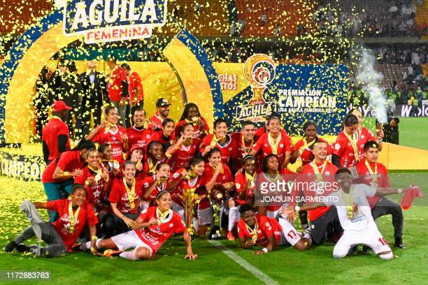 America de Cali's players celebrate with the trophy after winning the Colombian women's football league final match against Independiente Medellin at...