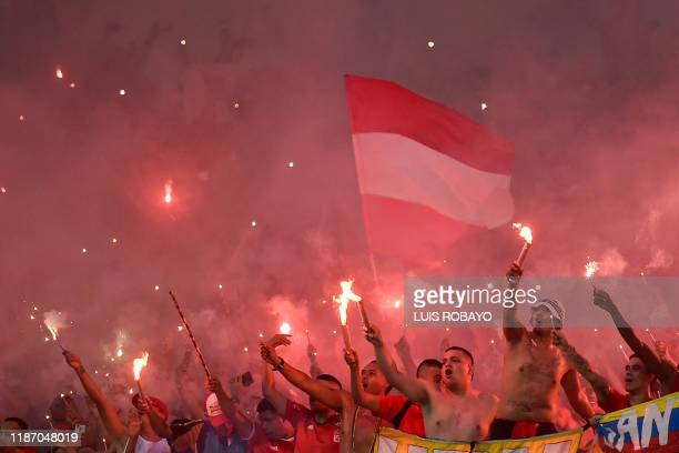 America de Cali's supporters celebrate after their team defeated Atletico Junior to win the Colombian First Division Football Championship at the...