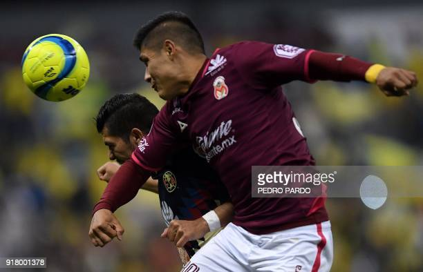 America forward Henry Martin vies for the ball with Morelia´s defender Jorgue Valadez during their Mexican Clausura tournament football match at...