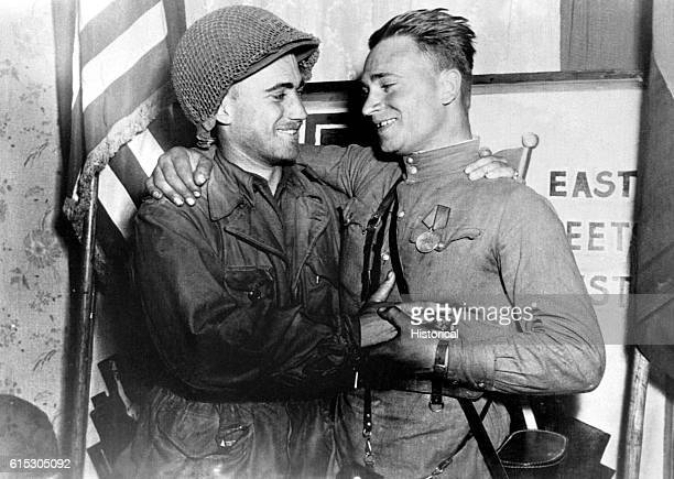 American 2nd Lt William Robertson and Lt Alexander Sylvashko Russian Army embrace in front of a sign reading 'East Meets West' symbolizing the...