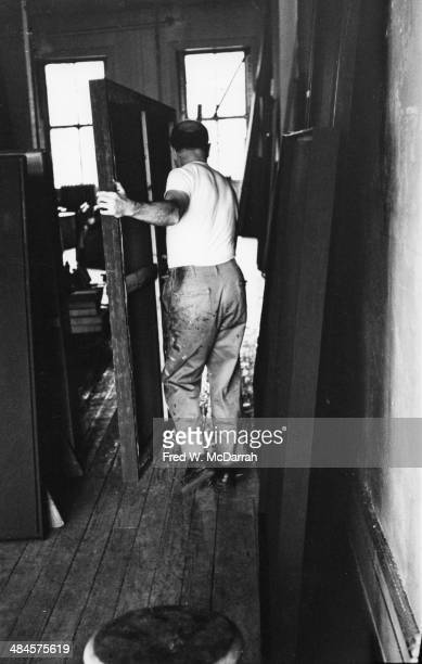 American Abstract artist Ad Reinhardt moves a painting in his studio New York New York March 1 1961