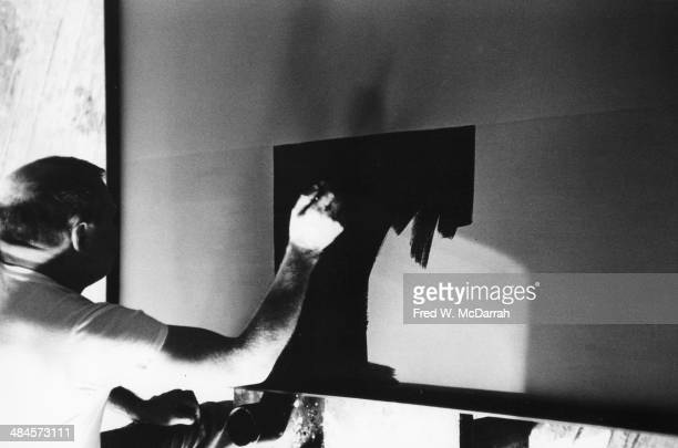 American Abstract artist Ad Reinhardt paints in his studio New York New York March 1 1961