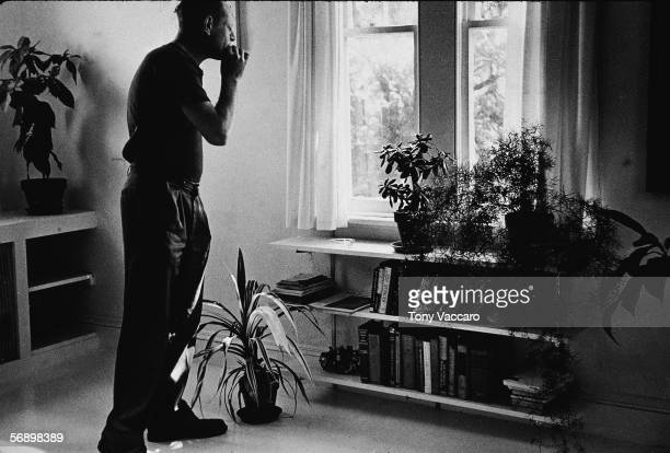 American abstract expressionist painter Jackson Pollock smokes a cigarette as he looks out a window of 'The Springs' East Hampton New York August 23...