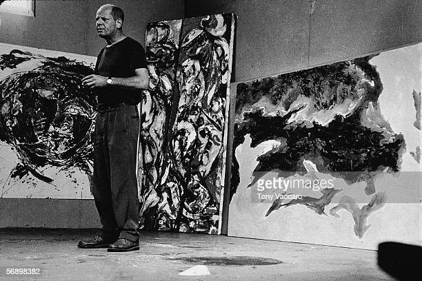 American abstract expressionist painter Jackson Pollock stands amid some large paintings in his studio at 'The Springs' East Hampton New York August...