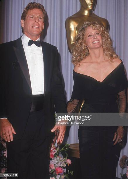 American acting couple Ryan O'Neal and Farrah Fawcett hold hands as they announce the winner of the Oscar for Film Editing at the 61st Annual Academy...