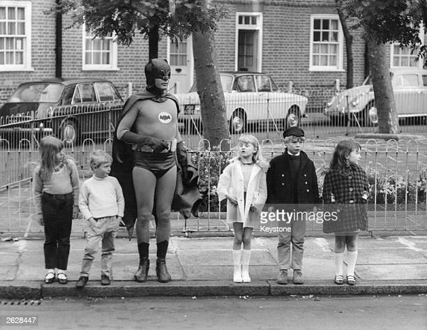 American actor Adam West as Batman making a road safety film with a group of child actors in Kensington London Original Publication People Disc HM0458