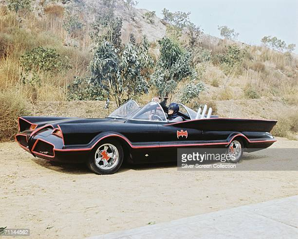 American actor Adam West as Bruce Wayne/Batman at the wheel of the Batmobile with passenger Burt Ward as Dick Grayson/Robin in the TV series 'Batman'...