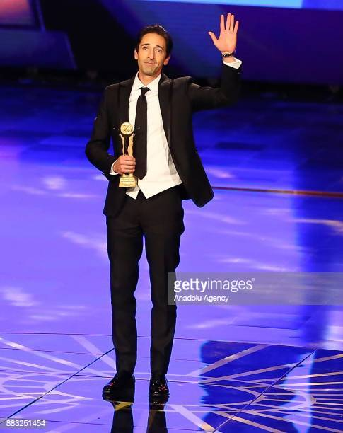 American actor Adrien Brody waves after receiving the honor award during the closing ceremony of the 39th Cairo International Film Festival in Cairo,...