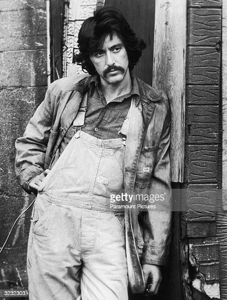 American actor Al Pacino leans against a building wearing overalls and a work coat in a still from director Sidney Lumet's film 'Serpico' The film...