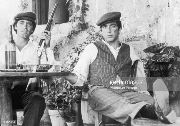 American actor Al Pacino sits with Italian actor Franco Citti holding a rifle at an outdoor table in director Francis Ford Coppola's film 'The...