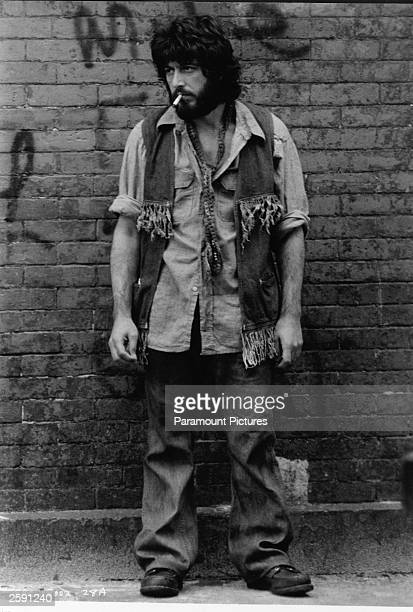American actor Al Pacino smoking a cigarette stands in front of a graffitied brick wall in a still from the film ''Serpico'' directed by Sidney Lumet...
