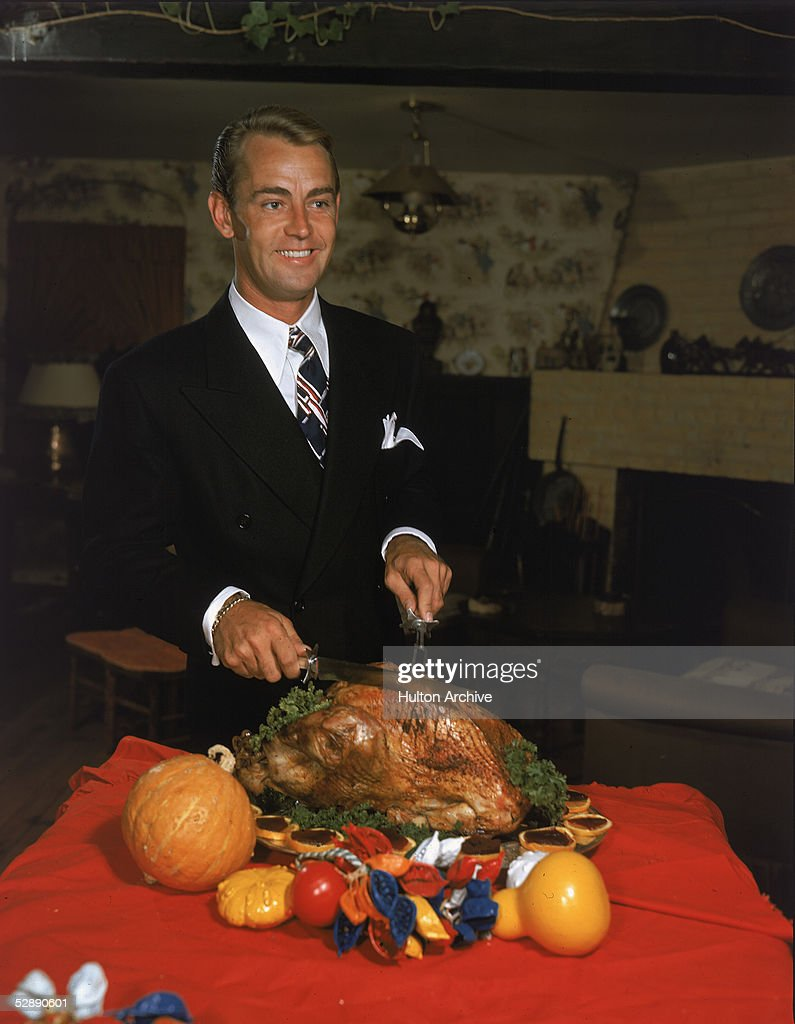 American actor Alan Ladd (1913 - 1964) carves a Thanksgiving turkey in a promotional portrait, 1950s.