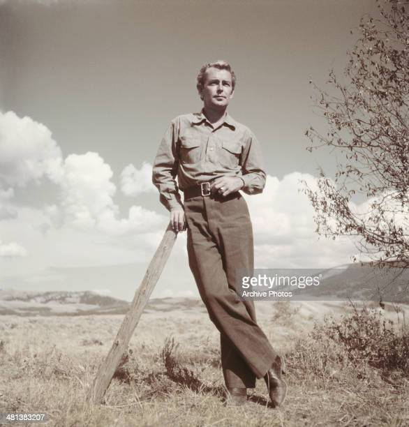 American actor Alan Ladd leaning on a post, circa 1955.