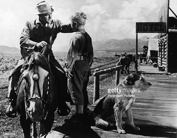 American actor Alan Ladd pats Brandon De Wilde's head as he prepares to leave on horseback in a still from the film, 'Shane,' directed by George...
