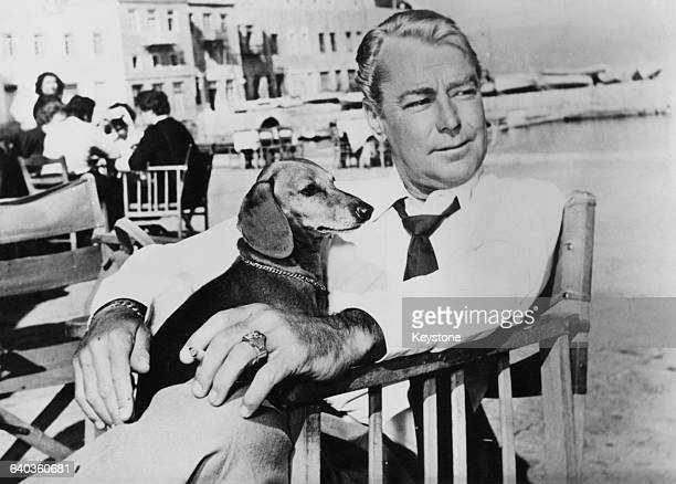 American actor Alan Ladd relaxes with his pet dog on the Greek island of Hydra, after location shooting of the exterior shots for the film 'Boy on a...