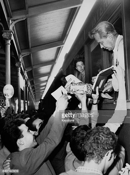 American actor Alan Ladd signs autographs for fans upon his arrival at Larissa Station in Athens, 25th September 1956. He is on location in Greece...