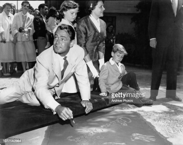 American actor Alan Ladd signs his name next to his handprints in wet cement outside Grauman's Chinese Theatre in Hollywood, 12th May 1954. He is...