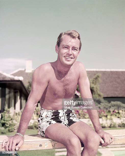 American actor Alan Ladd sitting on the diving board at a swimming pool, circa 1955.