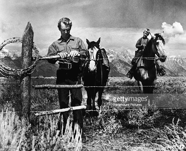 American actor Alan Ladd stands by a barbed wire fence as child actor Brandon De Wilde looks on from atop a horse in a still from the film 'Shane'...