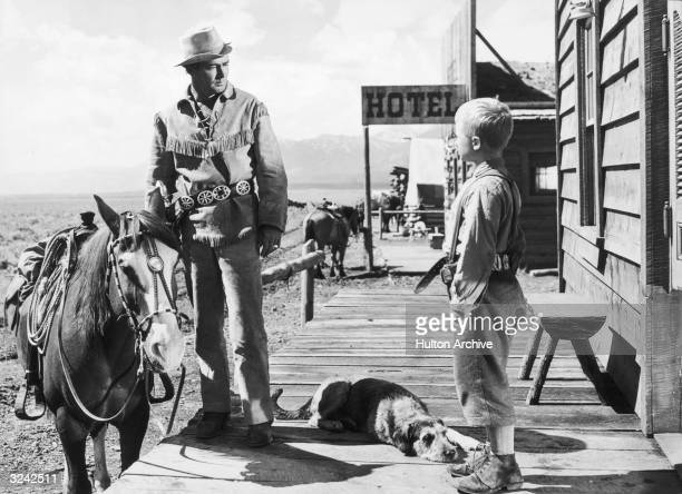 American actor Alan Ladd stands next to a horse and talks to child actor Brandon De Wilde in a still from director George Stevens' western film,...
