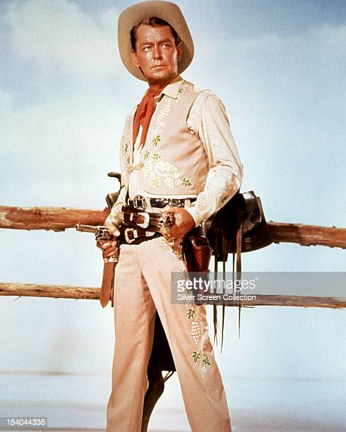 American actor Alan Ladd wearing a cowboy costume and holding a pair of pistols, circa 1958.