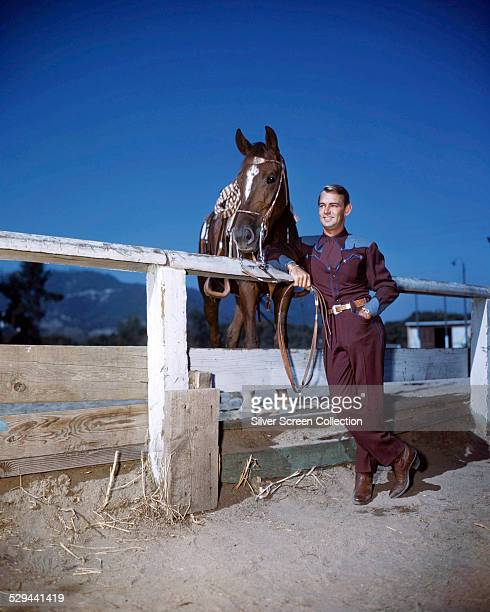 American actor Alan Ladd wearing a western outfit and posing next to a horse in a corral, circa 1950.