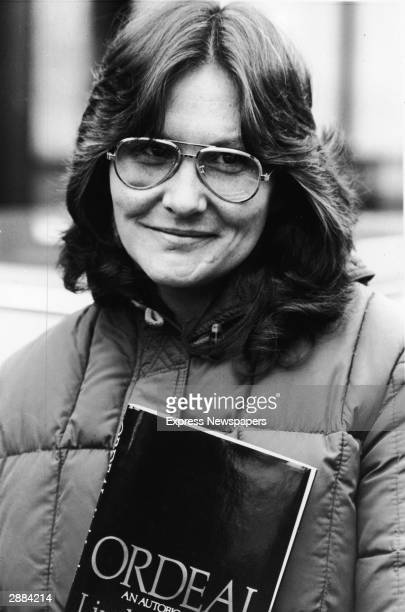 American actor and adult film star Linda Lovelace holds her book 'Ordeal' in London, England, April 4, 1981.