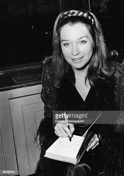 American actor and author Shirley MacLaine smiles as she signs a copy of her book during a book launch party at the Savoy Hotel, London, England,...