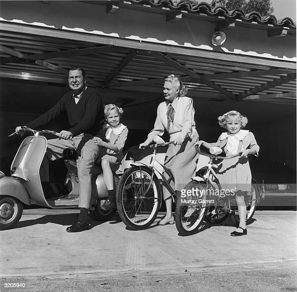 American actor and bandleader Phil Harris rides a moped as his wife American actor and singer Alice Faye and their two daughters Alice and Phyllis...