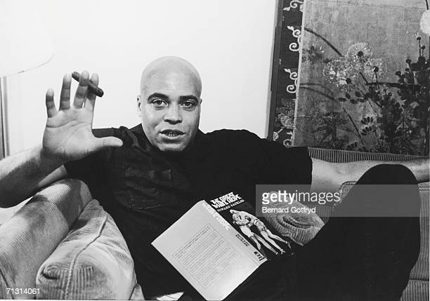 American actor and bass voice talent James Earl Jones sits on a corduroy couch with his legs crossed gestures with a cigar and speaks with an open...