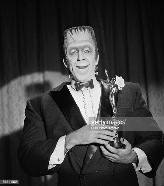 American actor and children's book author Fred Gwynne as 'Herman Munster' stands in a tuxedo before a curtain with an award trophy in a still from...